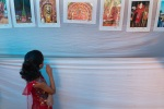 A girl watches theyyam photos that are exhibhited at the Theyyam venue
