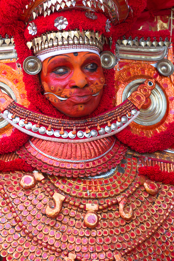 An old Theyyam dancer with a heavy costume